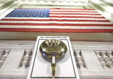FILE- In this May 17, 2018, file photo an American flag hangs above the bell podium on the floor of the New York Stock Exchange. The U.S. stock market opens at 9:30 a.m. EDT on Monday, June 4. (AP Photo/Richard Drew)