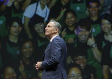 FILE - In this March 23, 2016, file photo, Starbucks CEO Howard Schultz walks in front of a photo of Starbucks baristas, at the coffee company's annual shareholders meeting in Seattle. Starbucks Corp. says Schultz is stepping down executive chairman later this month. Schultz, who oversaw the transformation of Starbucks into a global chain with more than 28,000 locations, had retired as CEO last year to focus on innovation and social impact projects as executive chairman. (AP Photo/Ted S. Warren, File)