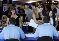 In this Thursday, June 21, 2018 photo, job applicants talks with representatives from Aldi at a job fair hosted by Job News South Florida, in Sunrise, Fla. The Labor Department said Friday, July 6, that the unemployment rate rose to 4.0 percent from 3.8 percent as more people began looking for work and not all of them found it. (AP Photo/Lynne Sladky)