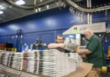 In this April 11, 2018, photo, production workers stack newspapers onto a cart at the Janesville Gazette Printing & Distribution plant in Janesville, Wis. Members of Congress are warning that newspapers in their home states are in danger of cutting coverage or going out of business if the United States maintains recently imposed tariffs on Canadian newsprint. (Angela Major/The Janesville Gazette via AP)