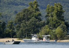 Emergency workers patrol an area Friday, July 20, 2018, near where a duck boat capsized the night before resulting in at least 13 deaths on Table Rock Lake in Branson, Mo. Workers were still searching for four people on the boat that were unaccounted for. (AP Photo/Charlie Riedel)