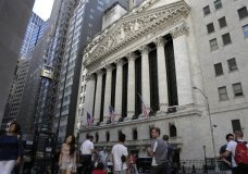 FILE - In this June 25, 2018, file photo, people walk outside the New York Stock Exchange in New York. U.S. stocks edged lower in early trading Monday, July 23, as losses in technology companies and retailers outweighed gains elsewhere. (AP Photo/Seth Wenig, File)