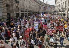 """Protestors hold banners during the 'Stop Trump' Women's March in London, Friday, July 13, 2018. U.S. President Donald Trump's pomp-filled welcome to Britain was overshadowed Friday by an explosive interview in which he blasted Prime Minister Theresa May, blamed London's mayor for terror attacks against the city and argued that Europe was """"losing its culture"""" because of immigration. (AP Photo/Tim Ireland)"""