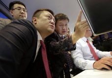 Opera Limited Chairman & CEO Yahui Zhou, third left, with secretary to the board An Da, left, and Shu Guan Wang, from China International Capital Corp., watch price quotes before Opera's IPO begins trading, at the Nasdaq MarketSite, in New York's Times Square, Friday, July 27, 2018. (AP Photo/Richard Drew)