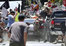 FILE - In this Aug. 12, 2017, file photo, people fly into the air as a vehicle drives into a group of protesters demonstrating against a white nationalist rally in Charlottesville, Va. Efforts to take down America's monuments honoring slain Confederate soldiers and the generals who led them gained explosive momentum following the deadly violence a year ago in Charlottesville. The vehicle plowed into a crowd protesting a gathering of white supremacists whose stated goal was to protect a statue of Gen. Robert E. Lee. (Ryan M. Kelly/The Daily Progress via AP, File)