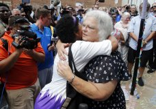 """Susan Bro, mother of Heather Heyer who was killed during last year's Unite the Right rally, embraces supporters after laying flowers at the spot her daughter was killed in Charlottesville, Va., Sunday, Aug. 12, 2018. Bro said there's still """"so much healing to do."""" She said the city and the country have a """"huge racial problem"""" and that if it's not fixed, """"we'll be right back here in no time."""" (AP Photo/Steve Helber)"""
