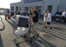 Kyle Crawford uses a shopping cart to carry bags of ice he purchased days after Hurricane Florence in Wilmington, N.C. Wednesday, Sept. 19, 2018. (AP Photo/Chuck Burton)