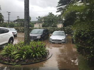 This Wednesday Sept. 12, 2018, photo shows floodwater in the parking lot of a condo complex at Kahana Village in Lahaina, Hawaii. Heavy rain and winds from a tropical storm downed trees, knocked out power and prompted evacuations of several homes on Hawaii's Maui island. (Lauren Greer via AP)