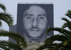 FILE- In this Sept. 5, 2018, file photo palm trees frame a large billboard on top of a Nike store that shows former San Francisco 49ers quarterback Colin Kaepernick at Union Square in San Francisco. Nike Inc. reports earnings Tuesday, Sept. 25. (AP Photo/Eric Risberg, File)
