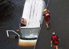 U.S. Coast Guard rescue swimmer Samuel Knoeppel, center, and Randy Haba, bottom right, approach to Willie Schubert of Pollocksville, N.C., on a stranded van in Pollocksville on Monday, Sept. 17, 2018, in the aftermath of Hurricane Florence. (AP Photo/Steve Helber)