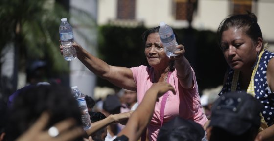 Residents hand out water bottles to Central American migrants making their way to the U.S. in a large caravan, at the main plaza in Tapachula, Mexico. (AP Photo/Moises Castillo)