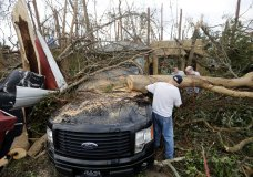 People cut away a tree that'll on a vehicle in the aftermath of Hurricane Michael in Panama City, Fla., Thursday, Oct. 11, 2018. (AP Photo/Gerald Herbert)