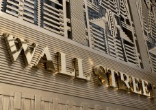 FILE- This April 24, 2018, file photo shows a sign for a Wall Street building in New York. The U.S. stock market opens at 9:30 a.m. EDT on Monday, Oct. 8. (AP Photo/Mark Lennihan)