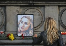 A woman places flowers next to a portrait of slain television reporter Viktoria Marinova during a vigil at the Liberty Monument in Ruse, Bulgaria, Monday, Oct. 8, 2018. Bulgarian police are investigating the rape, beating and slaying of a female television reporter whose body was dumped near the Danube River after she reported on the possible misuse of European Union funds in Bulgaria. (AP Photo/Vadim Ghirda)