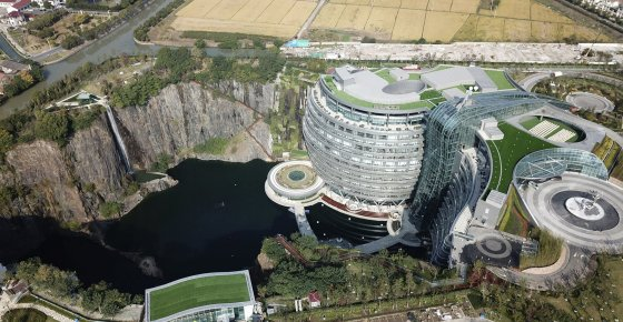 This Nov. 13, 2018, aerial photo and released on Thursday, Nov. 16, 2018 by Xinhua News Agency, shows the Intercontinental Shanghai Wonderland Hotel in Songjiang district of Shanghai, east China. The 18-story hotel has been built into the side of a huge hole in the ground left by a former put mine with sixteen of its floors below ground level. (Fang Zhe/Xinhua via AP)