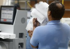 An employee at the Broward County Supervisor of Elections office prepares to sort ballots before being counted, Monday, Nov. 12, 2018, in Lauderhill, Fla. (AP Photo/Wilfredo Lee)
