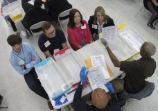 Workers at the Broward County Supervisor of Elections office, foreground, show Republican Democrat observers ballots during a hand recount, Friday, Nov. 16, 2018, in Lauderhill, Fla. Florida's acrimonious U.S. Senate contest is headed to a legally required hand recount after an initial review by ballot-counting machines showed Republican Gov. Rick Scott and Democratic Sen. Bill Nelson separated by fewer than 13,000 votes. (AP Photo/Wilfredo Lee)