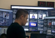 FILE - In this Oct. 17, 2018 file photo, a man works at his desk in front of monitors during a demonstration in the war room, where Facebook monitors election related content on the platform, in Menlo Park, Calif. Facebook and other social platforms have been waging a fight against online misinformation and hate speech for two years. With the U.S. midterm elections coming soon on Tuesday, Nov. 6, there are signs that they're making some headway, although they're still a long way from winning the war. (AP Photo/Jeff Chiu, File)