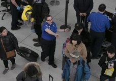 FILE- In this Jan. 7, 2019, file photo a TSA agent, center, directs passengers through a security checkpoint at New York's John F. Kennedy International Airport. The strain of a 34-day partial government shutdown is weighing on the nation's air-travel system, both the federal workers who make it go and the airlines that depend on them. Unions that represent air traffic controllers, flight attendants and pilots are growing concerned about safety with the shutdown well into its fifth week. (AP Photo/Mark Lennihan, File)
