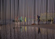 """FILE - In this Jan. 3, 2019, file photo, a woman takes a photo by the border fence between San Diego, Calif., and Tijuana, as seen from Mexico. The top House Republican says a bipartisan border security compromise that Congress hopes to produce doesn't have to include the word """"wall."""" (AP Photo/Daniel Ochoa de Olza, File)"""