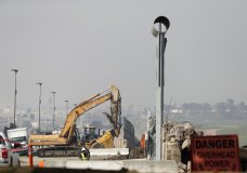 Crews work during demolition of border wall prototypes at the border between Tijuana, Mexico, and San Diego, Wednesday, Feb. 27, 2019, in San Diego. The government is demolishing eight prototypes of Donald Trump's prized border wall that instantly became powerful symbols of his presidency when they were built nine months after he took office. (AP Photo/Gregory Bull)