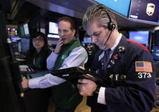 FILE- In this Tuesday, Jan. 29, 2019, file photo specialist Specialist Glenn Carell, center, and trader John Panin work on the floor of the New York Stock Exchange. The U.S. stock market opens at 9:30 a.m. EST on Thursday, Feb. 7. (AP Photo/Richard Drew, File)