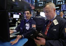 FILE- In this Feb. 8, 2019, file photo specialist Peter Mazza, left, and trader James Lamb work on the floor of the New York Stock Exchange. The U.S. stock market opens at 9:30 a.m. EST on Tuesday, Feb. 26. (AP Photo/Richard Drew, File)