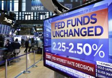 """A screen on the floor of the New York Stock Exchange shows the rate decision of the Federal Reserve, Wednesday, March 20, 2019. The Federal Reserve is leaving its key interest rate unchanged and projecting no rate hikes in 2019, dramatically underscoring its plan to be """"patient"""" about any further increases. (AP Photo/Richard Drew)"""