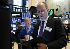 FILE- In this March 18, 2019, file photo trader Gordon Charlop, right, works on the floor of the New York Stock Exchange. The U.S. stock market opens at 9:30 a.m. EDT on Tuesday, March 25. (AP Photo/Richard Drew, File)