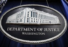 A sign for the Department of Justice hangs in the press briefing room Thursday, April 18, 2019, in Washington, at the Justice Department. Attorney General William Barr was to speak about the release of a redacted version of special counsel Robert Mueller's report during a news conference, (AP Photo/Patrick Semansky)
