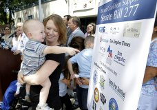 FILE - In this June 30, 2015, file photo, Jennifer Wonnacott holds her son, Gavin, as he points to a sign showing supporters of a measure requiring nearly all California school children to be vaccinated, at a news conference after the State Bill 277 was signed by Gov. Jerry Brown in Sacramento, Calif. State health officials say the number of measles cases in 2019 is up in California with cases stretching across 11 counties and affecting patients from 5 months to 55 years of age. Dr. Karen Smith, director of the California Department of Public Health, says more than 76% of patients were not vaccinated or didn't receive the recommended two doses of vaccine. Fourteen of those infected had traveled overseas to countries including Philippines, Thailand, India and Ukraine. Measles symptoms include high fever, a cough and a rash. (AP Photo/Rich Pedroncelli, File)