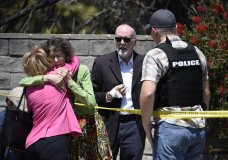 Two people hug as another talks to a San Diego County Sheriff's deputy outside of the Chabad of Poway Synagogue Saturday, April 27, 2019, in Poway, Calif. Several people have been shot and injured at a synagogue in San Diego, California, on Saturday, said San Diego County authorities. (AP Photo/Denis Poroy)