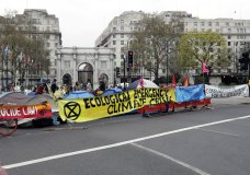 The road is blocked by demonstrators during a climate protest at Marble Arch in London, Tuesday, April 16, 2019. The group Extinction Rebellion is calling for a week of civil disobedience against what it says is the failure to tackle the causes of climate change. (AP Photo/Kirsty Wigglesworth)