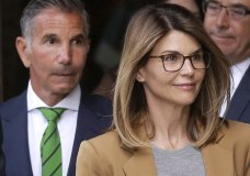 FILE - In this April 3, 2019 file photo, actress Lori Loughlin, front, and husband, clothing designer Mossimo Giannulli, left, depart federal court in Boston after facing charges in a nationwide college admissions bribery scandal. On Tuesday, April 9, Loughlin and Giannulli were among 16 prominent parents indicted on an additional charge of money laundering conspiracy in the case. (AP Photo/Steven Senne, File)