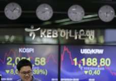 currency trader talks near the screens showing the Korea Composite Stock Price Index (KOSPI), left, and the foreign exchange rate between U.S. dollar and South Korean won at the foreign exchange dealing room in Seoul, South Korea, Friday, May 24, 2019. Asian shares were mostly lower on Friday as worries that the standoff between the U.S. and China over trade might expand put investors in a selling mood. (AP Photo/Lee Jin-man)