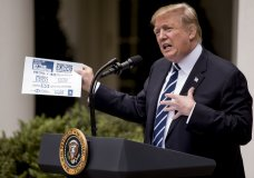 President Donald Trump holds up a stat sheet having to do with the Mueller Report as he speaks in the Rose Garden at the White House in Washington, Wednesday, May 22, 2019.(AP Photo/Andrew Harnik)