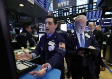 FILE - In this March 11, 2019, file photo specialist Peter Mazza, left, and trader James Riley work on the floor of the New York Stock Exchange. The U.S. stock market opens at 9:30 a.m. EDT on Wednesday, May 8. (AP Photo/Richard Drew, File)