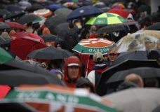 Spectators with umbrellas stroll as rain delayed the start of quarterfinal matches of the French Open tennis tournament at the Roland Garros stadium in Paris, Wednesday, June 5, 2019. (AP Photo/Christophe Ena)