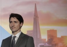 FILE - In this Feb. 8, 2018, photo, with an image of the San Fransisco skyline in the background, Canada's Prime Minister Justin Trudeau waits to speak at the AppDirect office in San Francisco. California picked up an important partner its long-running dispute with the Trump administration over vehicle emissions and fuel economy by announcing a deal with Canada to work on pollution reductions. (AP Photo/Jeff Chiu, File)