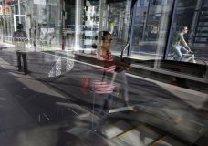 In this Monday, July 15, 2019 photo a passer-by, center, uses an escalator while emerging from a subway station, in Boston's Seaport district. On Friday, July 26, the Commerce Department issues the first estimate of how the U.S. economy performed in the April-June quarter. (AP Photo/Steven Senne)