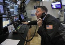 Trader Jonathan Muller works in his booth on the floor of the New York Stock Exchange, Monday, July 1, 2019. Stocks are rallying early Monday after the U.S. and China agreed to resume trade talks. (AP Photo/Richard Drew)