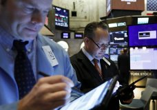 FILE - In this May 1, 2019, file photo traders Peter Mancuso, left, and Robert Arciero work on the floor of the New York Stock Exchange. The U.S. stock market opens at 9:30 a.m. EDT on Tuesday, July 9. (AP Photo/Richard Drew, File)