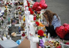 Gloria Garces kneels in front of crosses at a makeshift memorial near the scene of a mass shooting at a shopping complex Tuesday, Aug. 6, 2019, in El Paso, Texas. The border city jolted by a weekend massacre at a Walmart absorbed more grief Monday as the death toll climbed and prepared for a visit from President Donald Trump over anger from El Paso residents and local Democratic leaders who say he isn't welcome and should stay away. (AP Photo/John Locher)