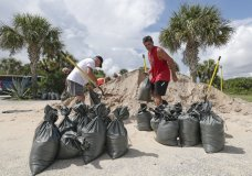 Residents of Flagler Beach, Fla., fill sandbags Friday, Aug. 30, 2019, to help protect their homes in preparation for Hurricane Dorian Friday, Aug. 30, 2019. (AP Photo/John Raoux)