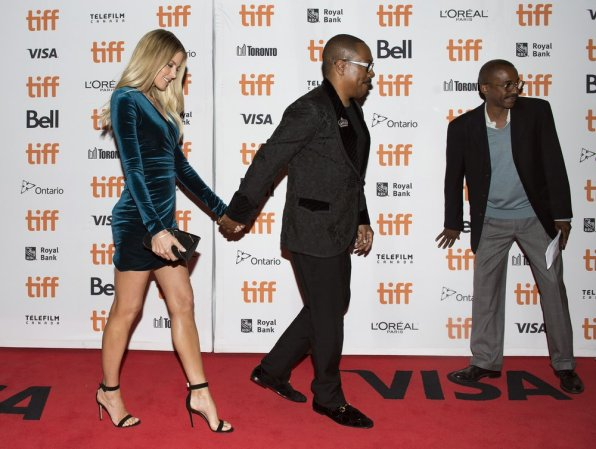 """Actor Eddie Murphy and his girlfriend Paige Butcher pose for photographs on the red carpet for the new movie """"Dolemite Is My Name"""" in Toronto, on Saturday, Sept. 7, 2019. (Nathan Denette/The Canadian Press via AP)"""