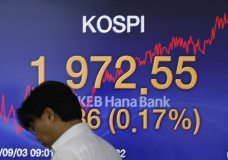 A currency trader walks by the screen showing the Korea Composite Stock Price Index (KOSPI) at the foreign exchange dealing room in Seoul, South Korea, Tuesday, Sept. 3, 2019. Asian stock markets were mostly lower Tuesday after investor jitters over U.S.-Chinese trade tension were revived by a report negotiators cannot agree on a schedule for talks this month. (AP Photo/Lee Jin-man)