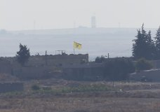 In this photo taken from the Turkish side of the border between Turkey and Syria, in Akcakale, Sanliurfa province, southeastern Turkey, a flag of Kurdish People's Protection Units, or YPG, flies on a building in the Syrian town of Tel Abyad, Tuesday, Oct. 8, 2019. Turkey's vice president says his country won't bow to threats in an apparent response to U.S. President Donald Trump's warning to Ankara about the scope of its planned military incursion into Syria aiming to create a zone that would allow Turkey to resettle Syrian refugees there. (AP Photo/Lefteris Pitarakis)