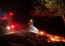 A firefighter battling the Kincade fire extinguishes a hot spot as strong winds send embers flying in Calistoga, Calif., on Tuesday, Oct. 29, 2019. Millions of people have been without power for days as fire crews raced to contain two major wind-whipped blazes that have destroyed dozens of homes at both ends of the state: in Sonoma County wine country and in the hills of Los Angeles. (AP Photo/Noah Berger)