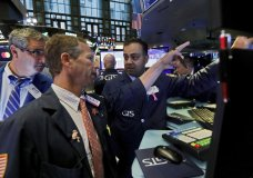 FILE - In this Oct. 7, 2019, file photo specialist Dilip Patel, right, work with traders at his post on the floor of the New York Stock Exchange. Banks led stocks broadly higher on Wall Street in afternoon trading Thursday, Oct. 10, placing the market on track to extend its gains from the day before. (AP Photo/Richard Drew, File)