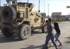 In this frame grab from video provided by Hawar News, ANHA, the Kurdish news agency, residents who are angry over the U.S. withdrawal from Syria hurl potatoes at American military vehicles in the town of Qamishli, northern Syria, Monday, Oct. 21, 2019. Defense Secretary Mark Esper said Monday in Afghanistan that U.S. troops will stay in eastern Turkey to protect Kurdish-held oil fields for at least the coming weeks and that he was discussing options to keep them there. (ANHA via AP)